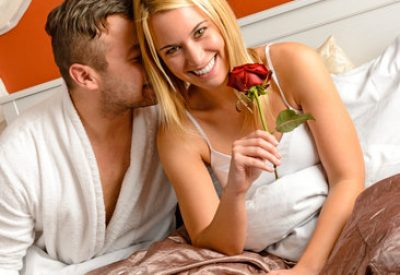 Cuddling couple cuddling bed motel room celebrating anniversary rose